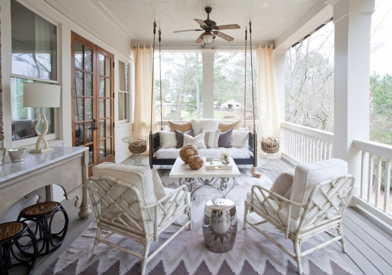 low wooden hanging sofa with white cushion and white pillows in white wooden floored porch