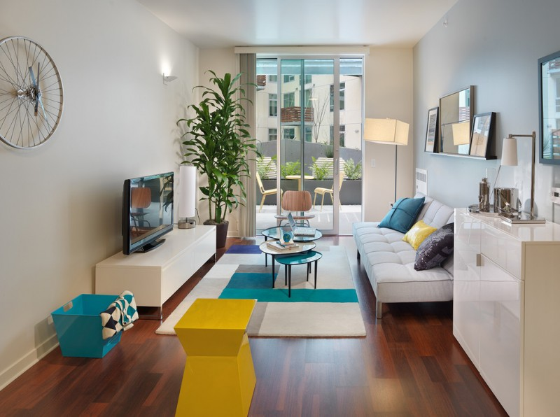 nesting cocktail table colorful area rug white tv cabinet blue basket glass doors grey curtain white couch colorful pillows table lamp floor lamp