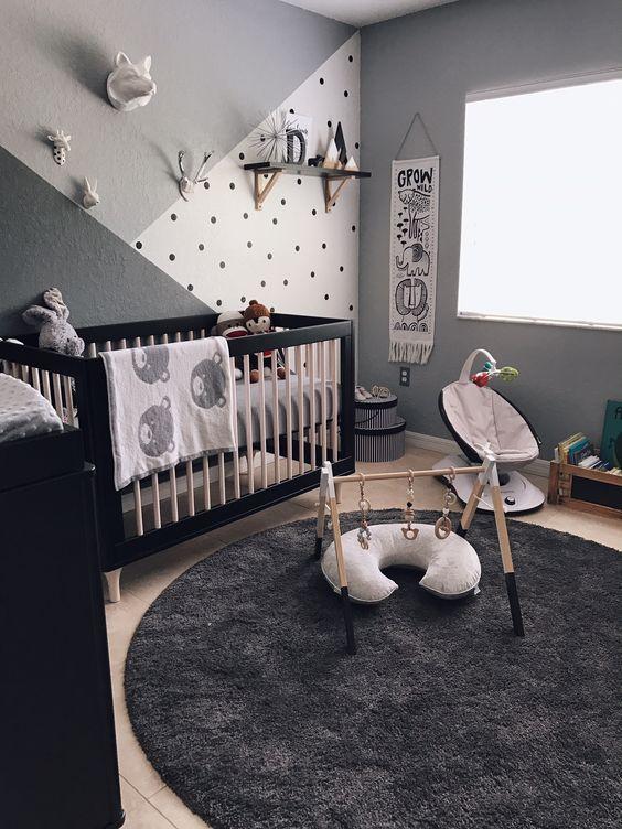 nursery with grey wall, brown wooden floor, black round rug, black cabinet, black wooden baby box