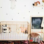 Nursery With White Walls, Brown Wooden Baby Box, Brown Leather Chair, Pink Colorful Rug