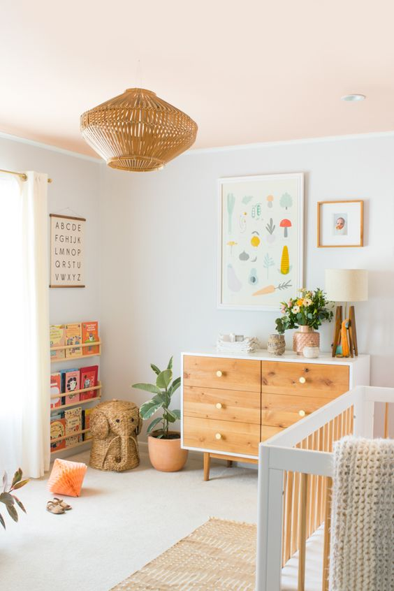 nursery with white walls, white floor, brown rug, white wooden baby box, brown wooden cabinet, brown rattan elephant, wooden lamp