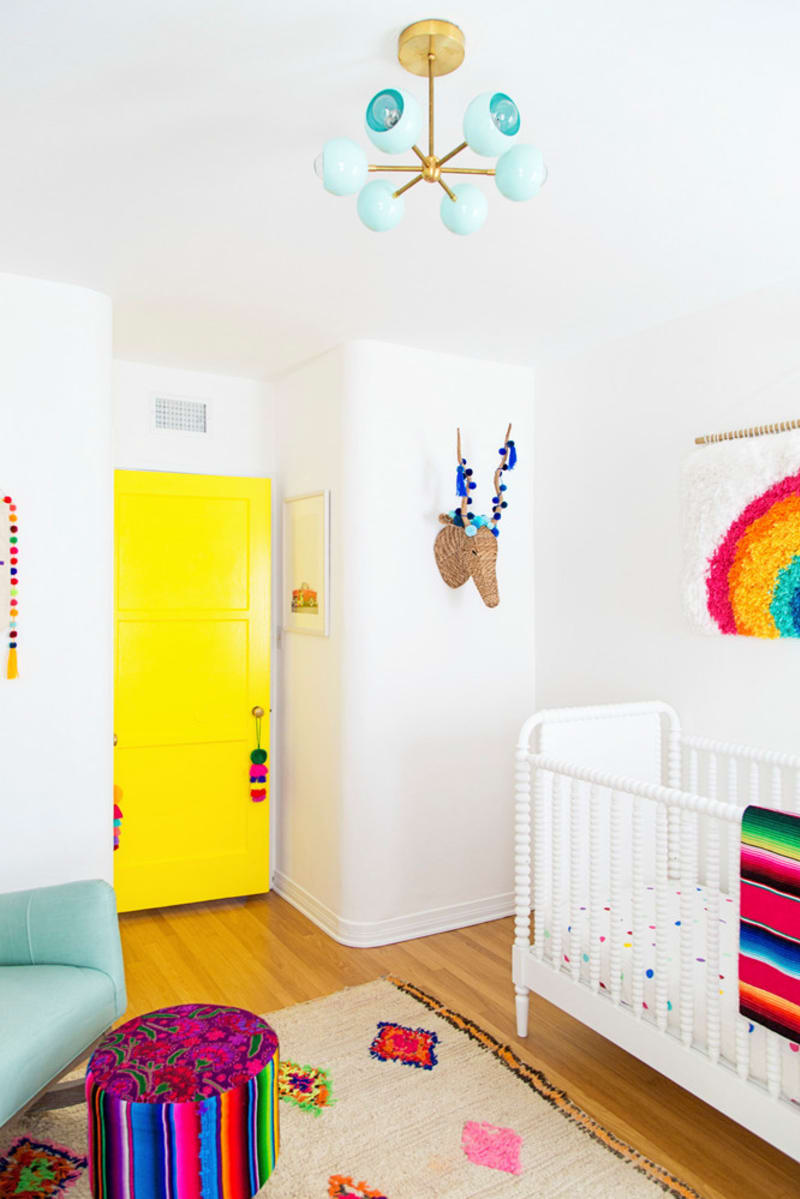 nursery with white walls, wooden floor, whit baby box, blue sofa, colorful ottoman, blue lamp