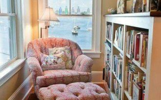 small home library with pink chair, ottoman, rug, white window frame, lamp, white wooden bookcase