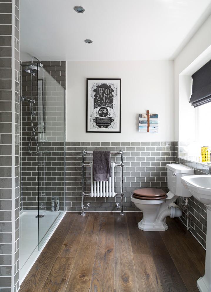 solid shower base grey subway walls tiles black and white artwork glass shower door grey valance window freestanding sink wooden floor