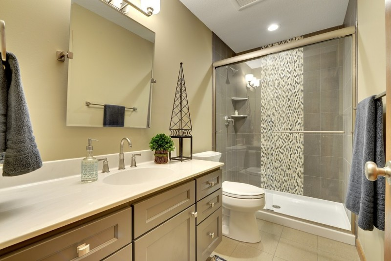 solid shower base wall mirror sliding glass shower doors recessed light wall sconce beige floating cabinet white top towel holder