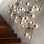 An Asymmetrical Sconce Structured In Brass And Hand Blown Glass On The Wall Near The Stairs