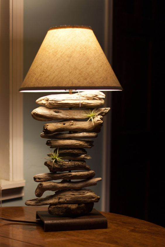 a bedside lamp with a pack of small branches linging on the pillar