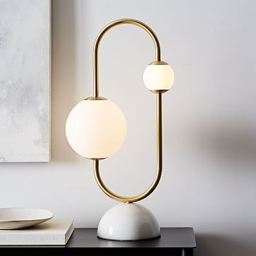 a bedside lamp with two sphere lamps big and small