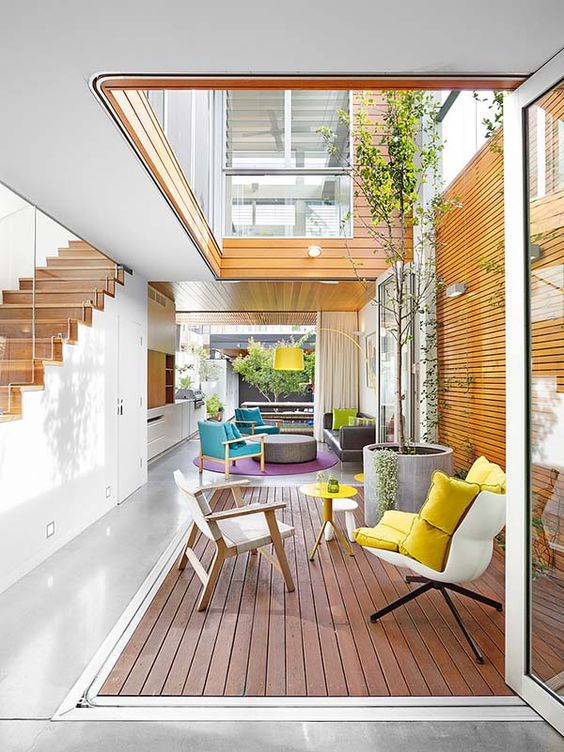 a space with wooden floor, wooden backdrop, a tree plants from concrete pot, high open ceiling, white chairs with yellow cushion