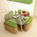 A Square Glass Top Table With Rattan Support, Triangular Chairs Made Of Rattan With Green Cushion