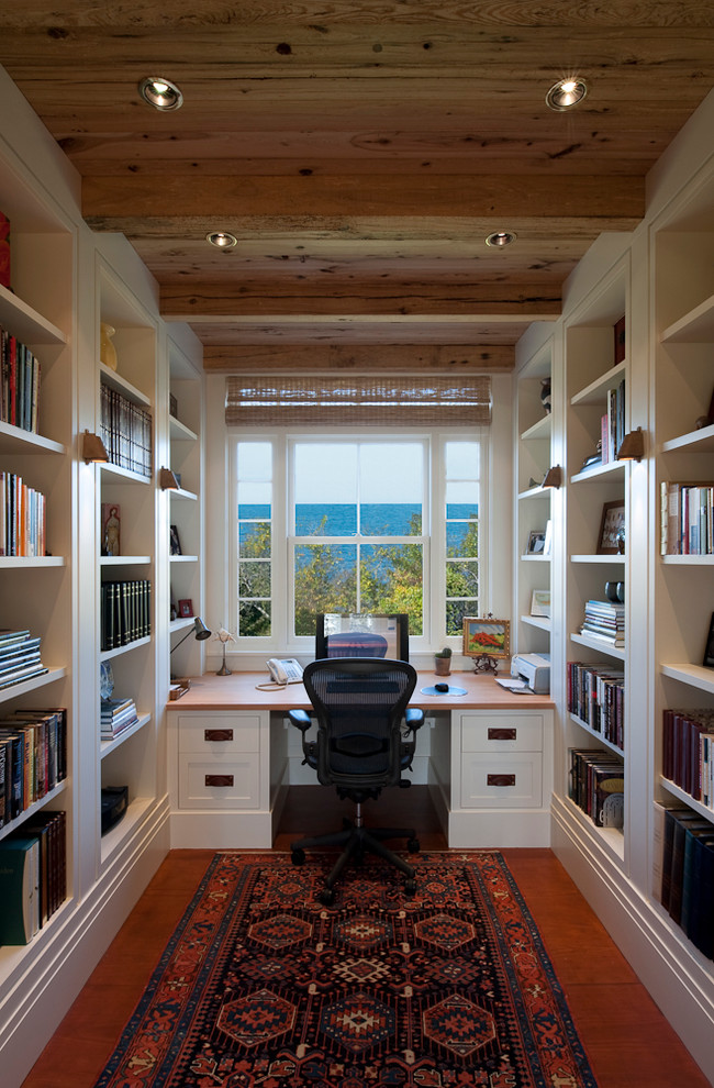 bamboo desk top patterned area rug glass windows wooden ceiling and beams bookshelves wooden floor white desk bamboo shade black office chair table lamp