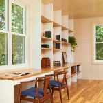Bamboo Desk Top Wooden Chairs With Dark Blue Cushions Wooden Shelves Glass Windows Long Desk Wooden Flooring Indoor Plant