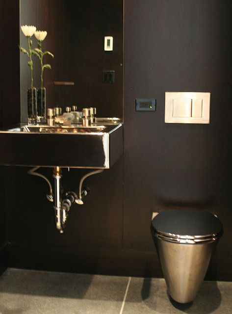 bathroom with black walls, stainless steel sink and toilet