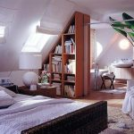 Bedroom With Vaulted Ceiling, Slanting In One Side, Slanting Bookshelves, Windows On Slanting Ceiling, White Chair, Rattan Bed, Bathroom