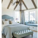 Bedroom With Wooden Floor, White Walls, Blue Rug, White Bench On The Windowsill With Blue Cushion, Bed With Blue Linen, Vaulted Ceiling, Chandelier
