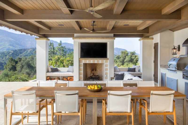 best outdoor ceiling fan fireplace wooden dining table wooden chairs brown floor tile outdoor kitchen appliances wall sconces built in benches