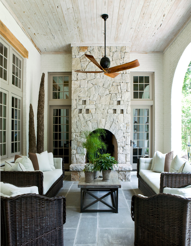 best outdoor ceiling fan stacked stone fireplace wall traditional fireplace dark rattan chairs dark rattan sofas wooden coffee table windows grey floor tile