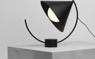 black triangular head of lamp that can move along the semi circle arc that can be adjusted on the base