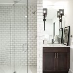 Craftsman Style Wall Sconce Dark Wooden Vanity White Subway Wall Tile White Mosaic Floor Tile Artwork Sink Wall Mirror Shower Head Undermount Sink Faucet