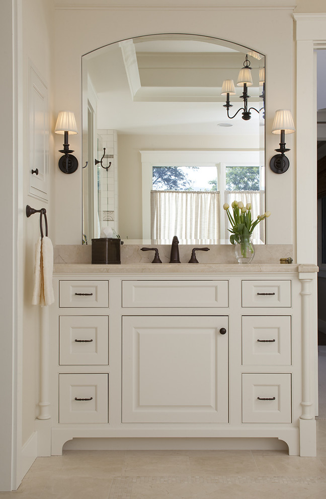 craftsman style wall sconce wall mirror white vanity old bronze faucet towel ring beige floor tile beige top sink