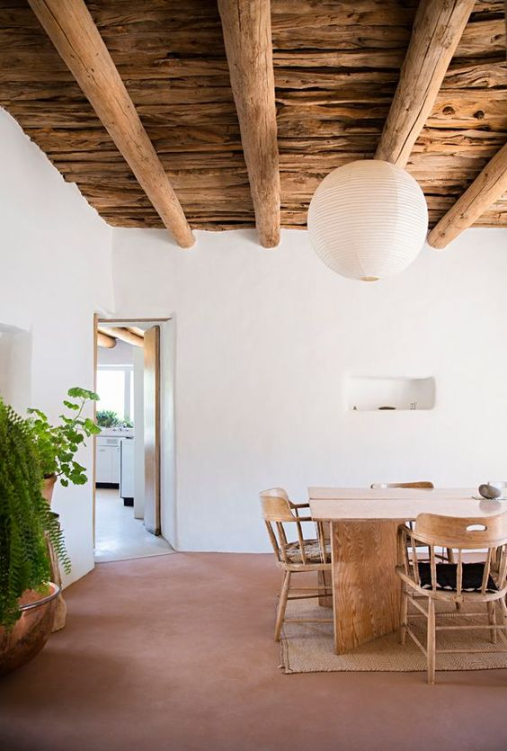 dining room with terracotta flooring, white walls, wooden dining set, wooden ceiling with wooden beams