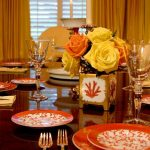 Dining Table With Glossy Dark Brown Table, Orange Plates, Orange And Yellow Flowers, Glasses
