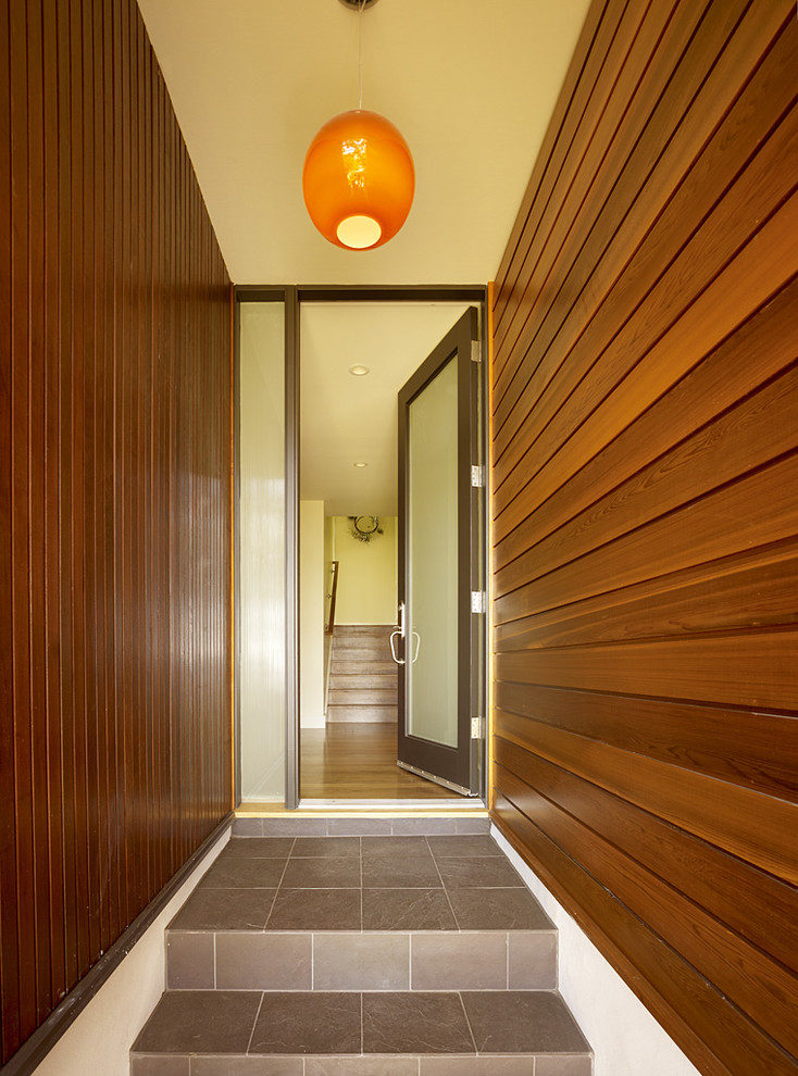entry door with one sidelight wooden vertical and hoizontal walls brown floor tiles pendnat lamp entry stairs translucent door