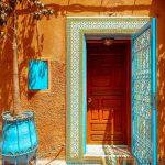 Front Door With Orange Wall, Bright Sky Blue Door, Windows, And Plants Pot, Brown Wooden Door
