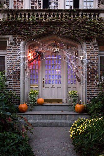 front porch with white wooden door, pumpkins, spiders, sconces, spider web