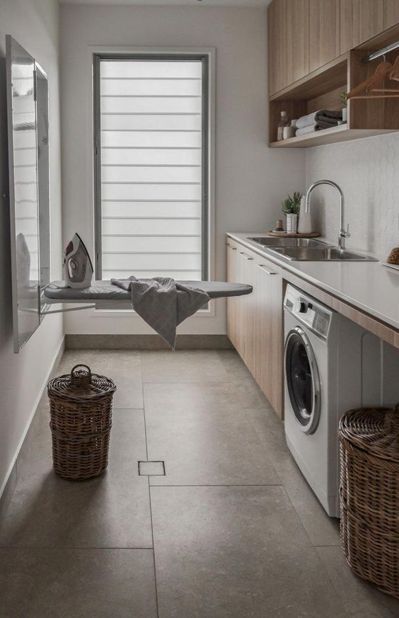kitchen with grey floor, brown cabinet, white marble top, sink, washing machine under, rattan baskets, ironing table near