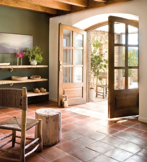 kitchen with terracotta tiles, wooden chair, wooden stool, wooden shelves, white walls, wooden beams on ceiling