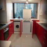 Kitchen With White Floor, Red Cabinet, White Kitchen Top, Washing Machine In The Cabinet