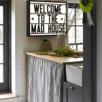 Kitchen With White Tiles, White Wooden Walls, Brown Wooden Kitchen Top, Washing Machine Under With Striped Curtain, White Sinks