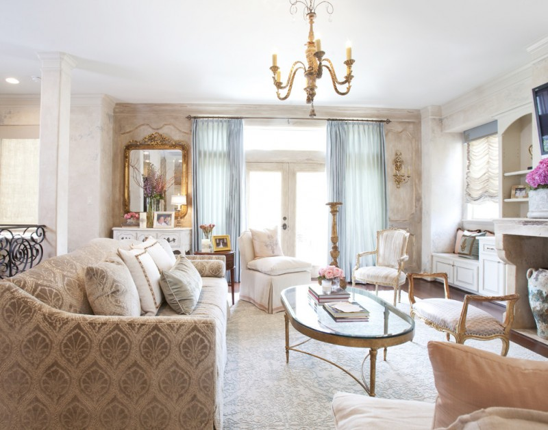 living room chair slipcovers beige patterned sofa glass coffee table area rug chandelier gold ornate wall mirror built in shelves bench blue curtains pillows