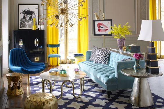 living room with blue sofa, blue chair, blue rug, glass top coffee table, gold ottoman, yellow curtain