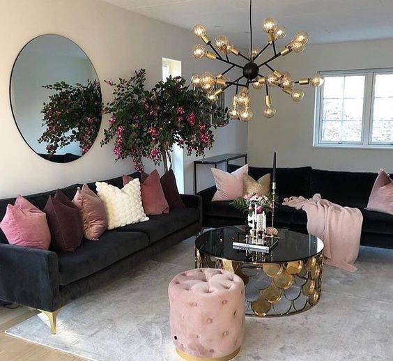 living room with light rgey rug, black sofa with pinkish pillows, coffee table with black glass top, plant, round mirror, pendant