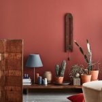 Living Room With Terracotta Wall, Grey Flooring, Rug, Beige Sofa, Low Wooden Table