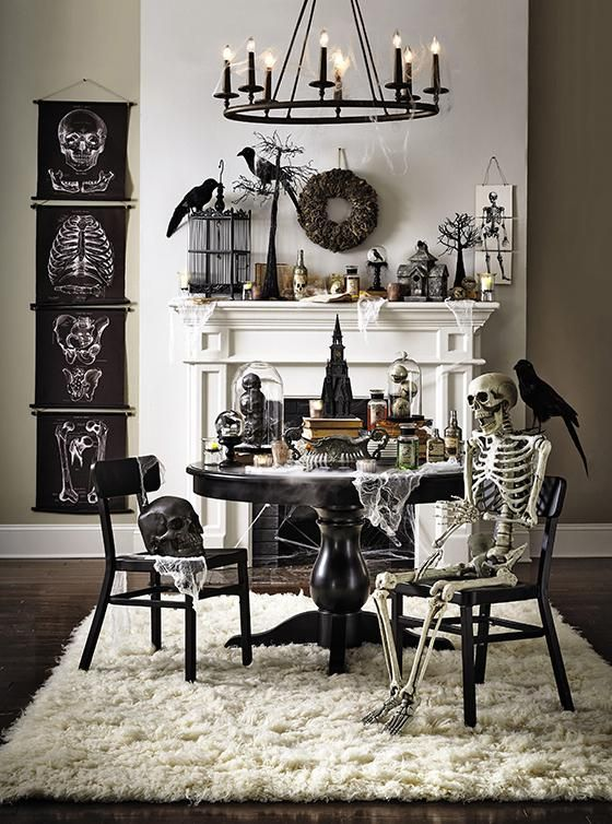 living room with white faux fur rug, black table with black chairs, white fireplace with halloween ornaments, black chandelier, skull