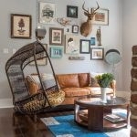 Living Room With Wooden Floor, Brown Leather Sofa, Round Wooden Coffee Table With Clear Glass Top, Brick Fire Place, Brown Rattan Swing With Yellow Cushion, Paintings, Fan Lamp