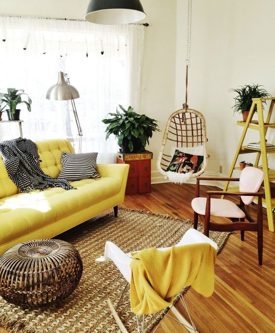 living room with wooden floor, white wall, yellor sofa, yellow wooden rack, white rocking chair, brown rug, rattan ottoman, silver lamps