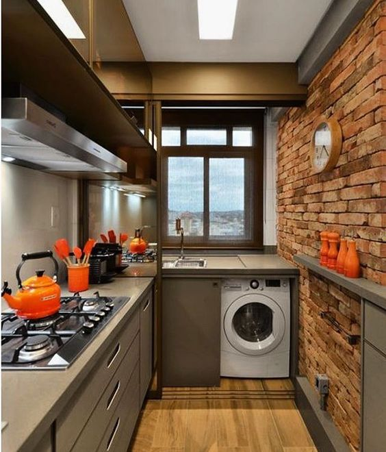 long kitchen with wooden floor, open brick wall, grey cabinet and top, washing machine under the top, near the sink