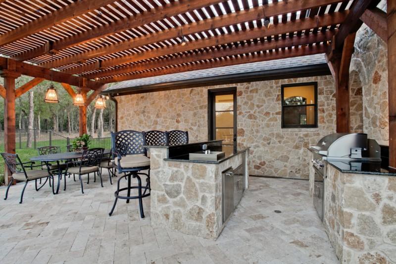 metal patio dining chairs cedar slats stovetop stone walls pendant lights black metal outdoor dining table black stools black granite countertops dishwasher grill glass d