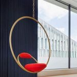Modern Swing With Goden Ring And A Chair With Red Small Cushion On The Ring