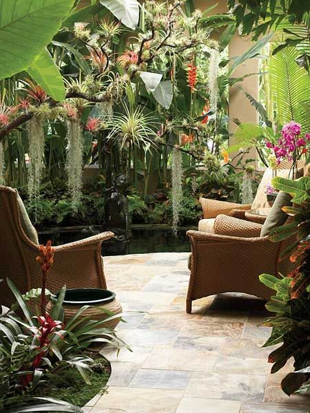 open atrium with patio tiles, rattan chairs, plants and flowers, ponds