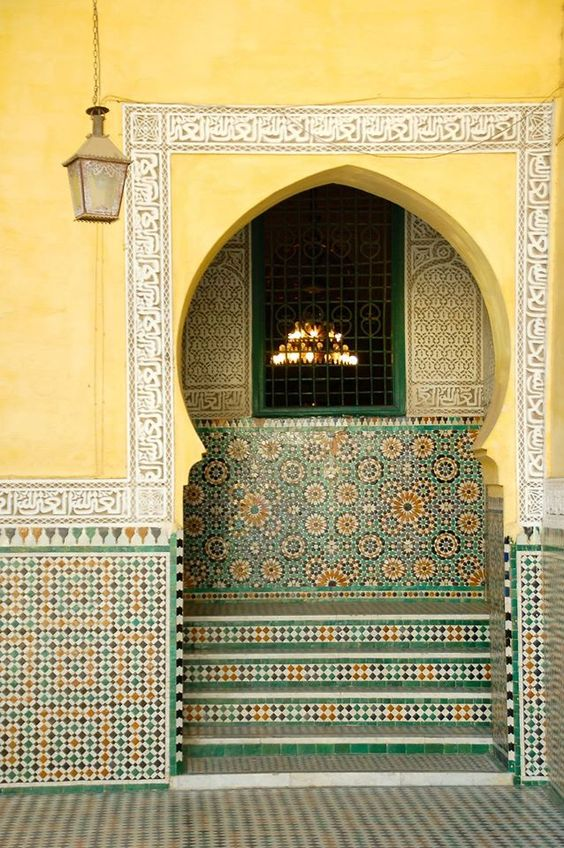 outside look of a moroccan house with yellow wall, yellow green tiles
