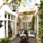 Patio Atrium With Black And White Rug, White Chairs With Grey Cushion, Beige Wall, Glass Windows To The House, Plants