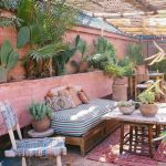 Patio With Pink Wall, Wooden Bench With Colourful Cushion, Wooden Coffee Table Wih White Top, Plants, Rattan Ceiling