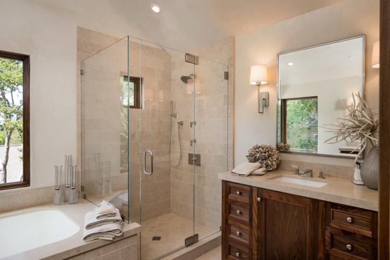 polished nickel mirror glass shower doors shower head wooden vanity sink faucet wall sconces built in bathtub windws beige tiles countertop