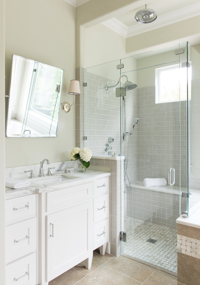 polished nickel mirror wall sconces wall mounted shower head glass shower doors grey wall tiles beige floor tile white vanity white countertop sink faucet