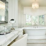 Polished Nickel Mirror White Acrylic Bathtub Windows White Shade White Vanity White Marble Countertop Chandelier White Chair Built In Shelves